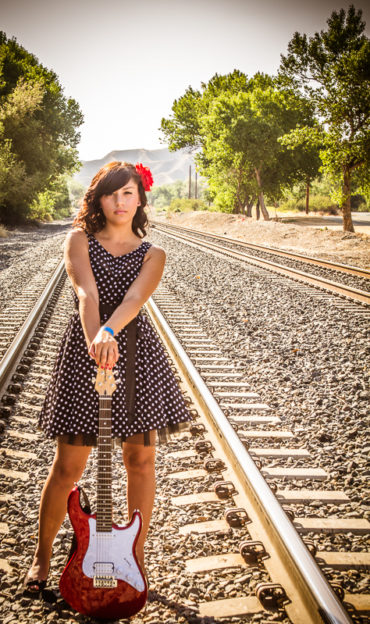 Quinceanera on railroad tracks with a red guitar