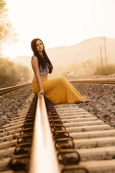 High Senior sitting on railroad tracks