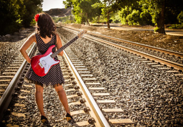 Quinceanera on railroad tracks with red guitar
